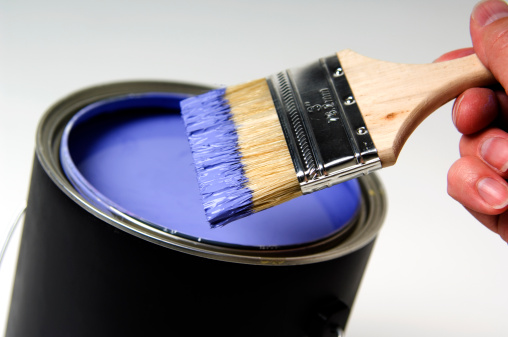 Man dipping paintbrush into purple paint can