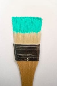 A stock photograph of an artists paint brush with fresh colorful paint on its bristles.